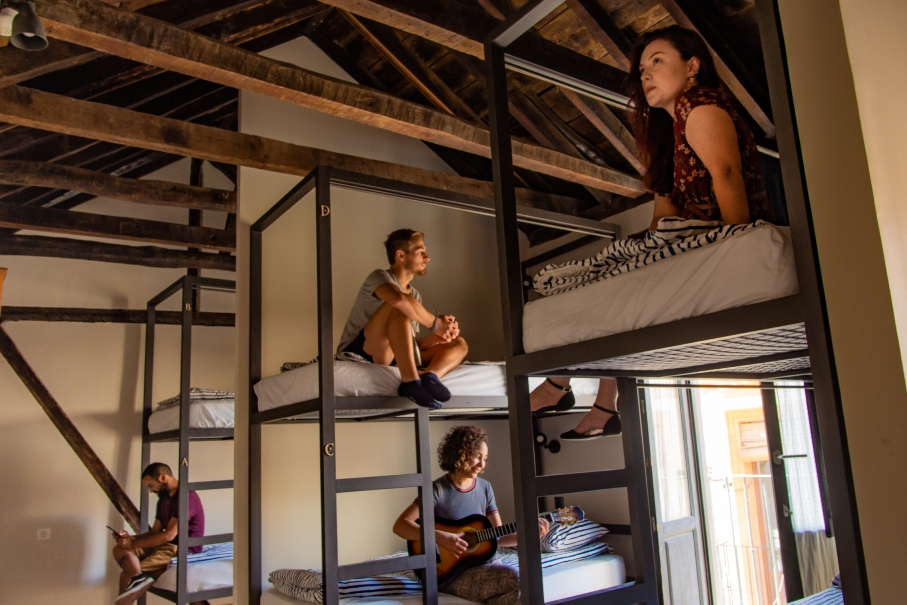 Guests relaxing on beds in 8 bed dorm with wooden beam cealing